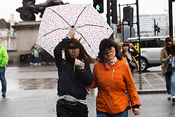 © Licensed to London News Pictures. 14/05/2015. London, UK. A woman holds onto her umbrella during heavy rain and wet and windy weather in Westminster, central London today. Photo credit : Vickie Flores/LNP