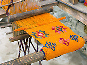 A handwoven woollen yathra skarf on a Tibetan style loom outside her farmhouse in the Tang Valley, Bumthang, Central Bhutan. Yathra is a hand woven fabric made from the wool of sheep and yak and is the most famous textile product of Bumthang. Yathra cloth is made into skarfs, jackets, table cloths and bags.