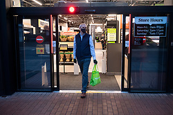 © Licensed to London News Pictures. 04/03/2021. London, UK. Customers exit the first AMAZON GO grocery store in the UK opens in Ealing, West London. Shoppers need to use app to shop inside the store and pick up groceries without stopping to pay. Photo credit: London News Pictures