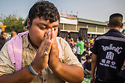 """15 MARCH 2014 - NAKHON CHAI SI, NAKHON PATHOM, THAILAND: A man prays after coming out of a trance state at the Wat Bang Phra tattoo festival. Wat Bang Phra is the best known """"Sak Yant"""" tattoo temple in Thailand. It's located in Nakhon Pathom province, about 40 miles from Bangkok. The tattoos are given with hollow stainless steel needles and are thought to possess magical powers of protection. The tattoos, which are given by Buddhist monks, are popular with soldiers, policeman and gangsters, people who generally live in harm's way. The tattoo must be activated to remain powerful and the annual Wai Khru Ceremony (tattoo festival) at the temple draws thousands of devotees who come to the temple to activate or renew the tattoos. People go into trance like states and then assume the personality of their tattoo, so people with tiger tattoos assume the personality of a tiger, people with monkey tattoos take on the personality of a monkey and so on. In recent years the tattoo festival has become popular with tourists who make the trip to Nakorn Pathom province to see a side of """"exotic"""" Thailand.   PHOTO BY JACK KURTZ"""
