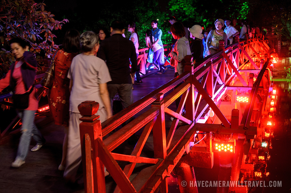 Tourists visiting The Huc Bridge (Morning Sunlight Bridge) at night. The red-painted, wooden bridge joins the northern shore of the lake with Jade Island and the Temple of the Jade Mountain (Ngoc Son Temple).