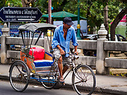 09 AUGUST 2018 - PHETCHABURI, PHETCHABURI, THAILAND: A rickshaw driver pedals over the the Phetchaburi River flowing through Phetchaburi town. The river is about a meter below flood stage. The Phetchaburi River flows from Kaeng Krachan Dam to the Gulf of Siam through several towns including Ban Lat, Phetchaburi (the capital of Phetchaburi province) and Ban Laem. Government officials have warned residents of those towns that their towns will flood because the reservoir behind the dam is approaching capacity. Ban Lat and Phetchaburi could be flooded for several weeks. Residents of Ban Laem have been warned that their community could be inundated for over a month. Dams in Kanchanaburi province, west of Phetchaburi, are also approaching capacity and flooding is also expected in that area.   PHOTO BY JACK KURTZ