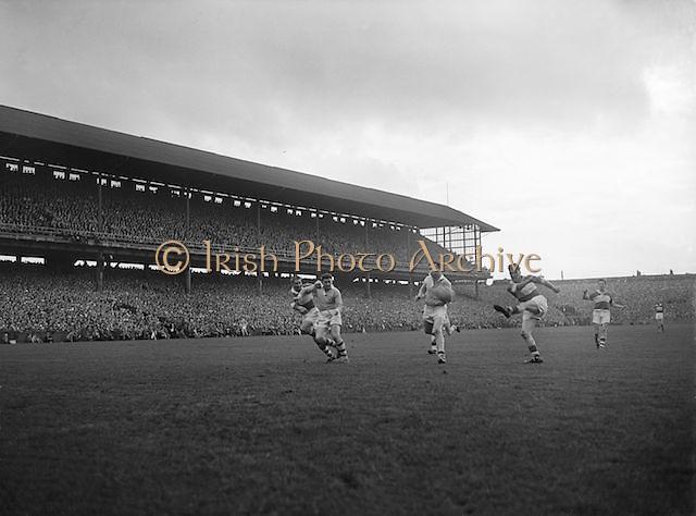 Derry kicks the ball flying towards the goal during the All Ireland Senior Gaelic Football final Dublin vs Derry in Croke Park on 28th September 1958. Dublin 2-12 Derry 1-9.