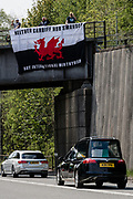 MERTHYR TYDFIL, WALES - 04 MAY 2020: Merthyr Town football fans pay tribute to Phillip Fly by displaying their flags during Mr Flys funeral procession.
