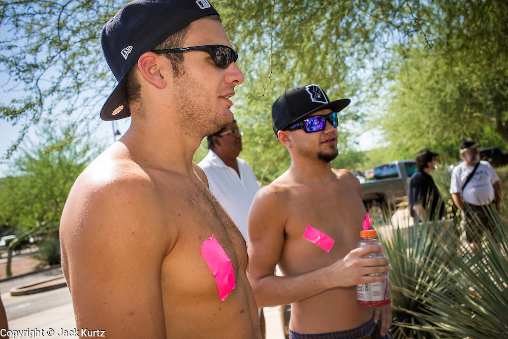 26 MARCH 2012 - PHOENIX, AZ: JOHN BOYCE, left, and STEPHAN PETERSON, both from Goodyear, AZ, wait to march in the topless protest in Phoenix. About 40 people marched through central Phoenix Sunday to call for a constitutional amendment to give women the same right to go shirtless in public that men have. The Phoenix demonstration was a part of a national Topless Day of Protest. Phoenix prohibits women from going topless in public so protesters, women and men, covered their nipples and areolas with tape. The men did it to show solidarity with the women marchers.    PHOTO BY JACK KURTZ