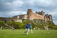 Bamburgh, Northumberland, England, UK. 23rd May 2021. Bamburgh CC host Wolsingham CC from Durham, against the impressive backdrop of Bamburgh Castle in Northumberland.