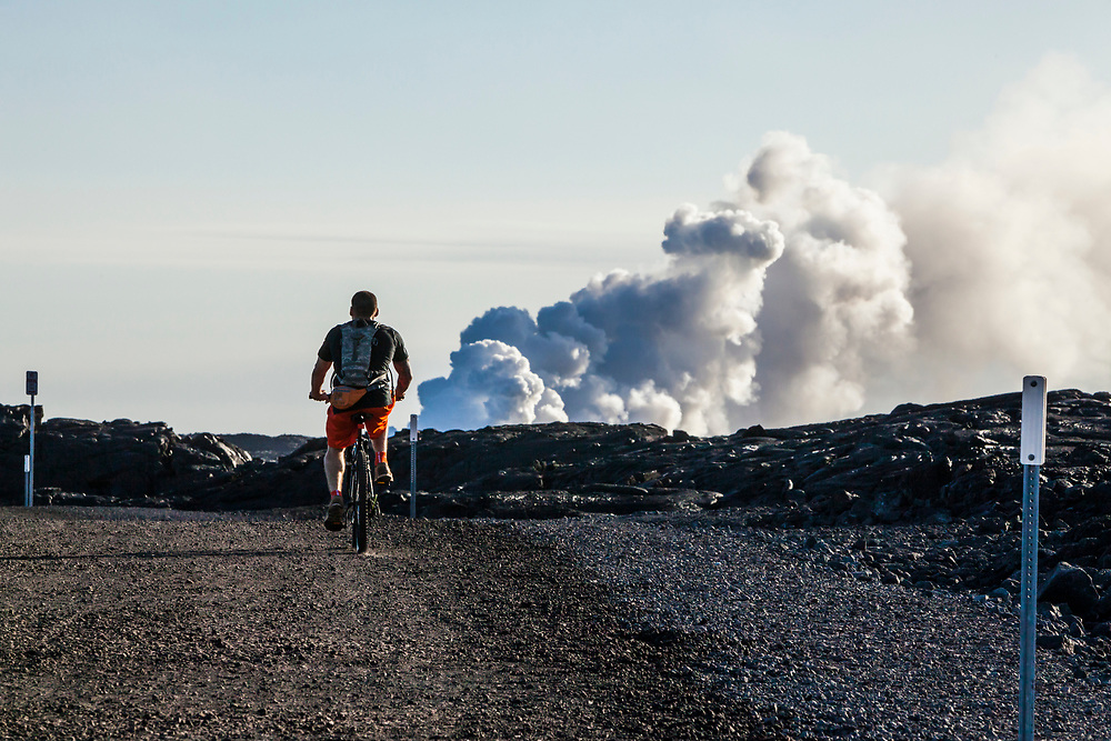 A bicyclist riding the Chain of Craters road out to the lava entry point into the ocean, Puna, Hawaii, USA.