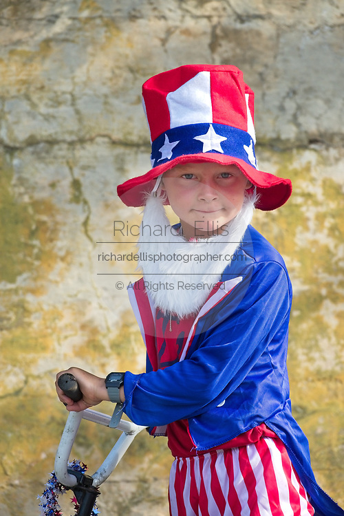 A young boy dressed as Uncle Sam rides his bike during the annual Sullivan's Island Independence Day parade July 4, 2017 in Sullivan's Island, South Carolina. The tiny affluent sea island hosts a bicycle and golf cart parade through the historic village.
