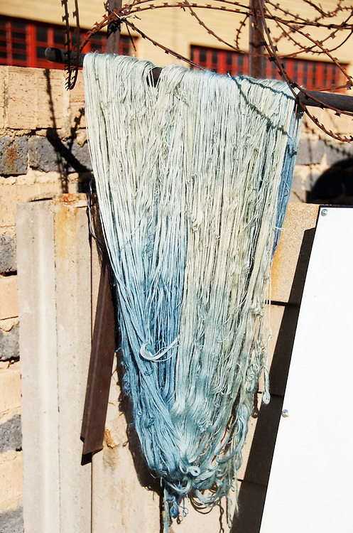 A skein of mohair yarn dyed in indigo and natural mordant hangs to dry in the sun. Indigo dye and bogolan workshop held with Aboubakar Fofana in Johannesburg, South Africa
