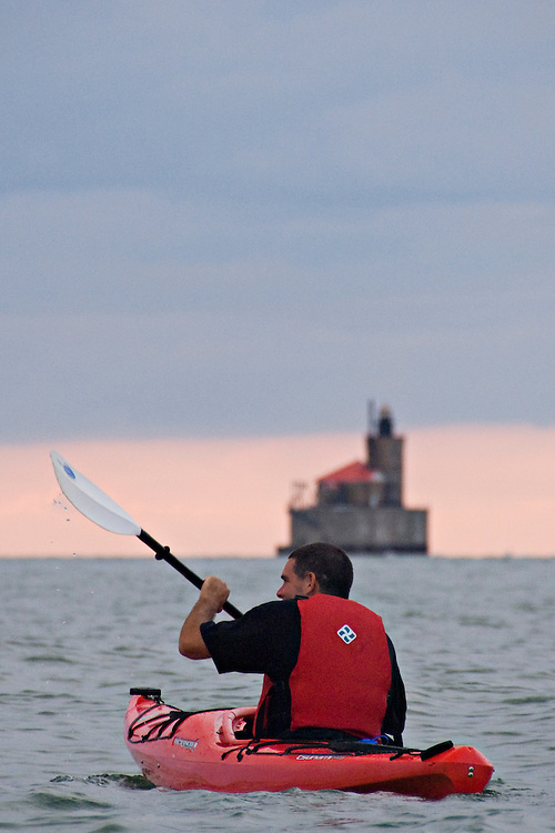 Kayaking on Lake Huron with the Port Austin Lighthouse in background in Port Austin Michigan.