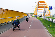 In Utrecht fietst een gehandicapte man op een aangepaste driewielige ligfiets over de Gele Brug tussen Utrecht en Leidsche Rijn.<br /> <br /> In Utrecht a disabled man cycles on a special tricycle over the yellow bridge between Utrecht and Leidsche Rijn.