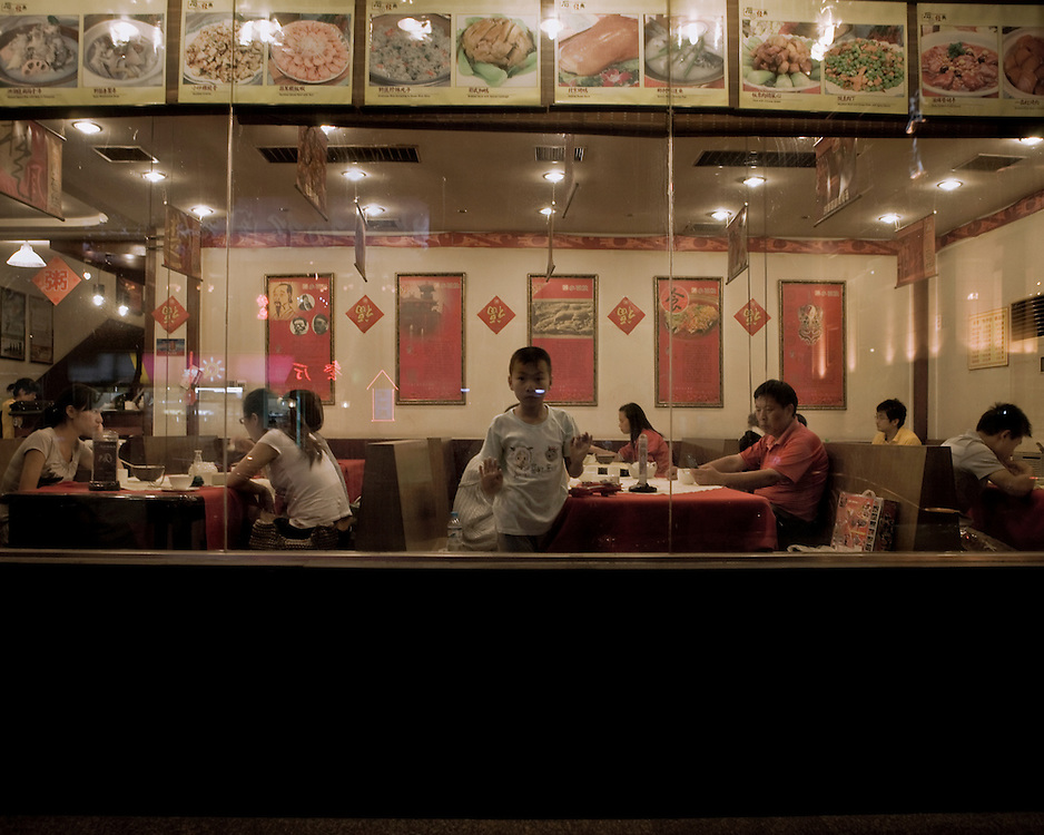A young boy looking out through the glass from a Chinese restaurent