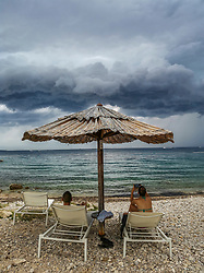 THEMENBILD - Zwei Touristen sitzen unter einem Sonnenschirm an der Küste der kroatischen Insel Rab am 04. August 2020 in Kroatien und beobachten die Wolken eines aufziehenden Unwetters // THEMES PICTURE - Tourists are sitting under a sun shade and watch the clouds of an uprising severe weather on the coast of the mediterranean sea on the island of Rab, Croatia, on 04 August 2020. EXPA Pictures © 2020, PhotoCredit: EXPA/ Erwin Scheriau