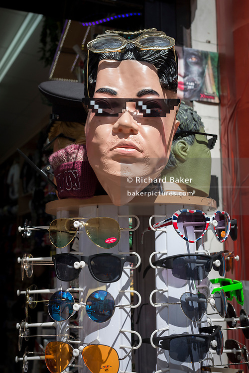 The face of North Korean leader Kim Jong-un appears on face masks outside a tourist trinket retailer selling sunglasses on Oxford Street, on 1st May, in London, England.