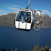 A mountain biker rides the Skyline scenic gondola to the Queenstown Mountain Bike track on Ben Lomond above  Queenstown..Queenstown is nestled on the shores of the crystal clear waters of Lake Wakatipu in the Central Otago region of the South Island of New Zealand..Queenstown is New Zealand's premier tourist destination providing an abundance of year round outdoor activities for both young and old. Queenstown, Central Otago, South Island, New Zealand. 18th May 2011. Photo Tim Clayton..