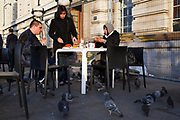 Tourists outside McDonalds are besieged by hungry pigeons, who loiter around for crumbs and directly attack the food on the table. South Bank, London, UK.