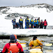 Kayakers approach the rocky shore for a landing at Petermann Island on the Antarctic Peninsula.