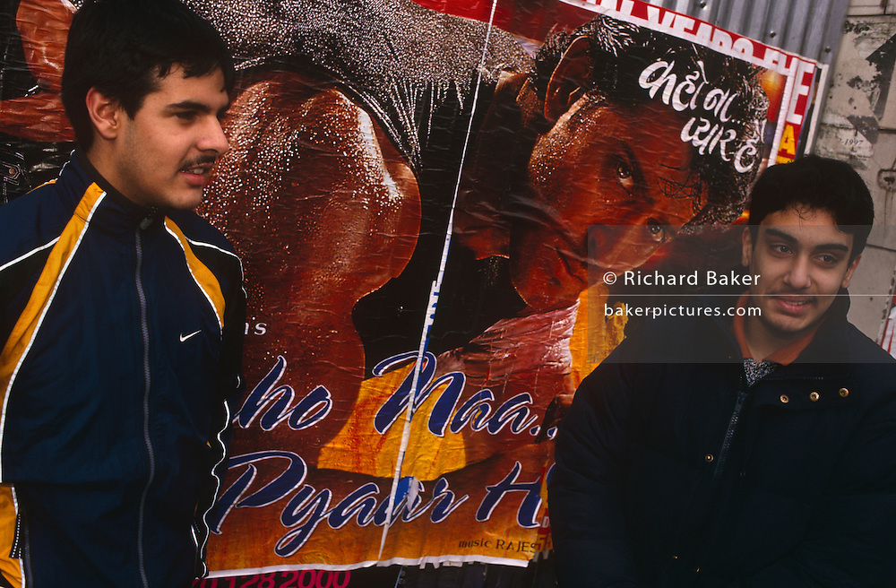 Two young British Asian men stand in front of a Bollywood action hero poster, while waiting for a bus in Southhall, West London, England. The lads are in their early twenties and are dressed against the cold European winter. The muscular Indian man in the movie poster is in his prime, posing as a tough guy and making a serious face towards the viewer, his rippling biceps wet with sweat. We see two ordinary young men living the harsh reality of life in a big English city, with all the pressures, paradoxes and cultural differences of India or Bangladesh, and that of multicultural Britain. It may be sunny but the biting winter day is raw with cold.