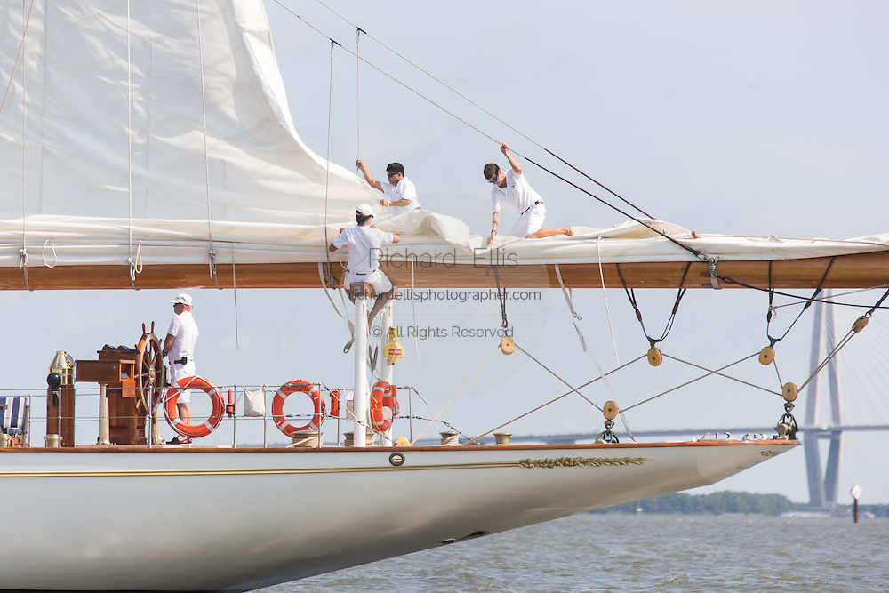 Deck hands rig the sails on the 196-foot sailing yacht Germania Nova as it sails Charleston Harbor June 26, 2013 in Charleston, South Carolina.