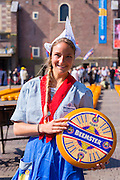 Dutch girl Kaasmeisje wearing traditional costume and Beemster Gouda cheese, Alkmaar cheese market, The Netherlands