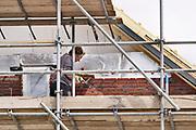 Nederland, Afferden, 15-5-2020 Nederlandse bouwvakkers zijn bezig met het metselen van de buitenmuur van huizen . Foto: Flip Franssen
