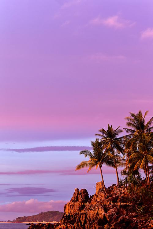 Purple Haze: A spectacular tropical coastal sunset casts the rocky coast line in a purple haze, on Ko Lanta – Thailand.