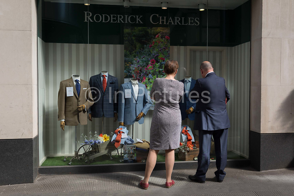 A man and woman look at the display of a menswear outfitters  in the City of London, the capitals financial district aka the Square Mile, on 17th May 2018, in London, UK.