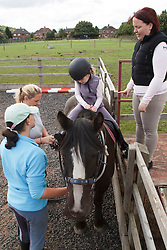 Mother with visual impairment and instructor with daughter at riding lesson.
