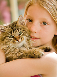 Close up of young girl hugging kitten