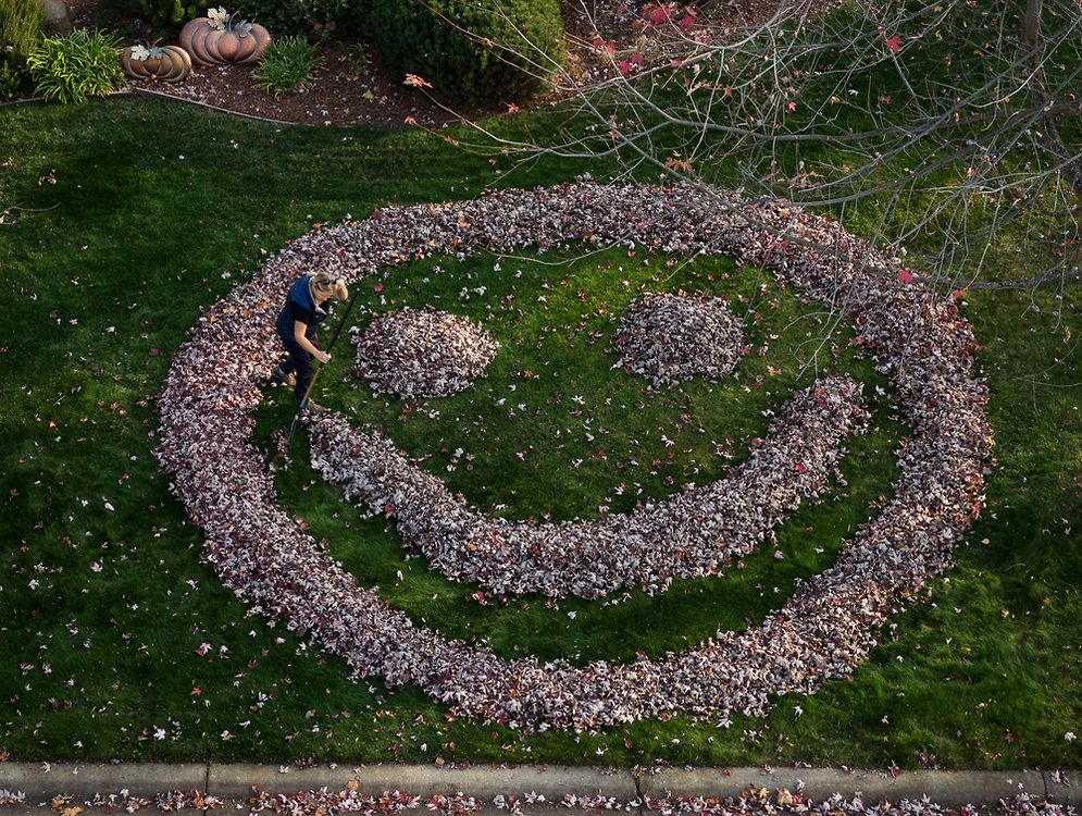 """Cheryl Goldsworthy rakes up leaves in her front yard in the shape of a smiley face at her El Dorado Hills home, Tuesday, Nov. 19, 2019. """"It Makes a task lighter to put smiles on people's faces,"""" said Goldsworthy."""