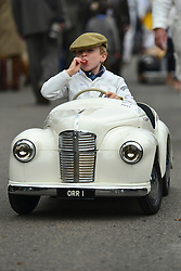 © Licensed to London News Pictures. 15/09/2013. Chichester, UK Young competitors return to there paddock  sucking lollipops after completing in the Settrington Cup. People enjoy the atmosphere at the last day of 2013 Goodwood Revival. The event recreates the glorious days of motor racing and participants are encouraged to dress in period dress. The revival is the only event of its kind to be staged entirely in the nostalgic time capsule of the 1940s, 50s and 60s Photo credit : Stephen Simpson/LNP.