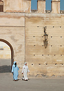Women walk through the gated entrance to the medina of Fes, Morocco