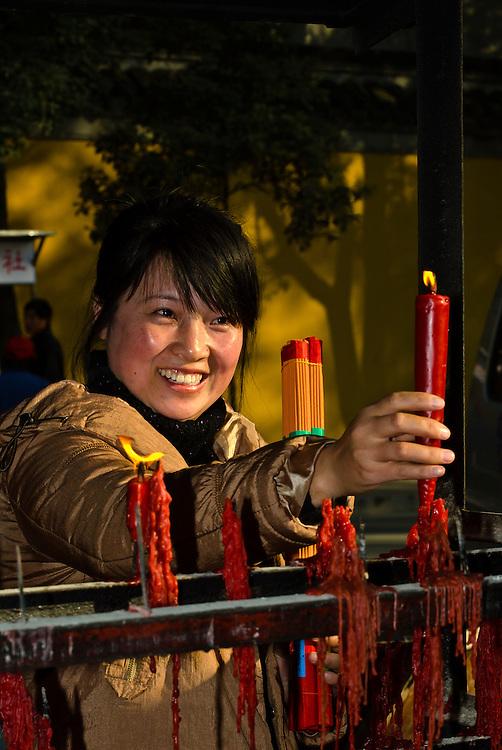 People lighting candles and incense, Jinshan Temple, Jinshan Park, Zhenjiang, China