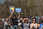 """Brooklyn, NY - 17 April 2016. A man holds two signs in support of Bernie  Sanders. Vermont Senator Bernie Sanders, who is running as a Democrat in the U.S. Presidential primary elections, held a campaign """"get out the  vote"""" rally in Brooklyn's Prospect Park."""