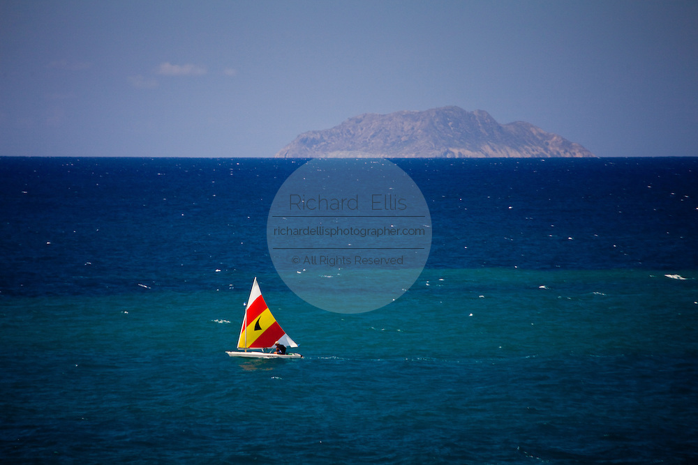 Small sailboat off Rincon Puerto Rico with Isla Desecheo on the horizon (photo by Charleston SC photographer Richard Ellis)