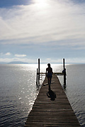 Young female figure silhouette walking towards camera, down a Jetty on the banks of a lake at dawn, showing vanishing point. Working Gaucho Fazenda in Rio Grande do Sul, Brazil.