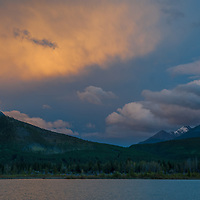 A sunset Lights up clouds over Vermillion Lakes and the Canadian Rockies in Banff National Park, Alberta, Canada.