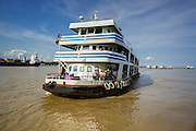 """17 JUNE 2013 - YANGON, MYANMAR:   A Dala bound ferry approaches the pier on the Yangon River. The ferry to Dala opposite Yangon on the Yangon River is the main form of transportation across the river. Every day the ferry moves tens of thousands of people across the river. Many working class Burmese live in Dala and work in Yangon. The ferry is also popular with tourists who want to experience the """"real"""" Myanmar. The rides takes about 15 minutes. Burmese pay about the equivalent of .06¢ US for a ticket.  Foreigners pay about the equivalent of about $4.50 US for the same ticket.  PHOTO BY JACK KURTZ"""