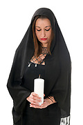 Religious Faith woman lights a candle