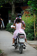 Young girl with her hair made up and in her best clothes, riding behind her Mother on a motorbike. Mekong River in Cai Be, Tien Giang Province, Vietnam
