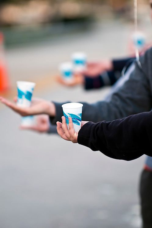 Close up of volunteers hands offering water during a Marathon. Use of selective focus. Lots of Copyspace.