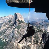 ROCK CLIMBING. John Fischer ascending rope to Glacier Point, Yosemite NP. Half Dome bkg. (MR)