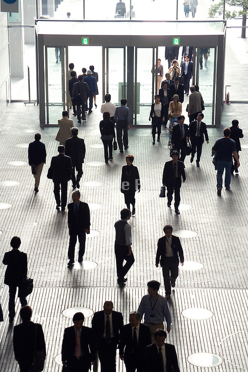 businesspeople arriving and leaving a large office building