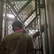A detainee having a discussion with a guard in Camp 6 at the Guantánamo Bay Detention Facility in Guantanamo Bay, Cuba. The detainees held in this facility were captured after the attacks on the United States on September 11, 2001. In 2009 US president Barack Obama ordered the closure of the facility, yet to date it still remains open. These Photos were reviewed by military officials before release.