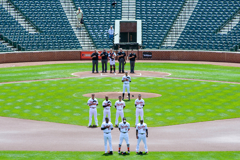 Baltimore, MD - April 29, 2015: The Baltimore Orioles and Chicago White Sox stand during a recorded version of the National Anthem at an empty Oriole Park at Camden Yards on April 29, 2015. Orioles center Fielder Adam Jones blows a bubble with his gum. The civil unrest in Baltimore has forced the game between the Chicago White Sox and Baltimore Orioles to be closed to the public and moved to the afternoon. (Matt Roth for ESPN)
