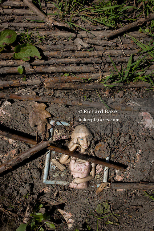 Doll trodden into soil in risk averse playground called The Land on Plas Madoc Estate, Ruabon, Wrexham, Wales.