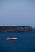 The ferry to Manly passes North Head, Sydney Harbour, Australia at dusk.