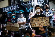 """OAKLAND, CA - JUNE 03: Demonstrators hold placards during a """"Sit Out the Curfew"""" protest against the death of George Floyd who died on May 25 in Minneapolis whilst in police custody, along a street in Oakland, California on June 3, 2020. - US protesters welcomed new charges against Minneapolis officers in the killing of African-American man George Floyd -- but thousands still marched in cities across the country for a ninth straight night, chanting against racism and police brutality. (Photo by Philip Pacheco/Agence-France Presse/AFP)"""