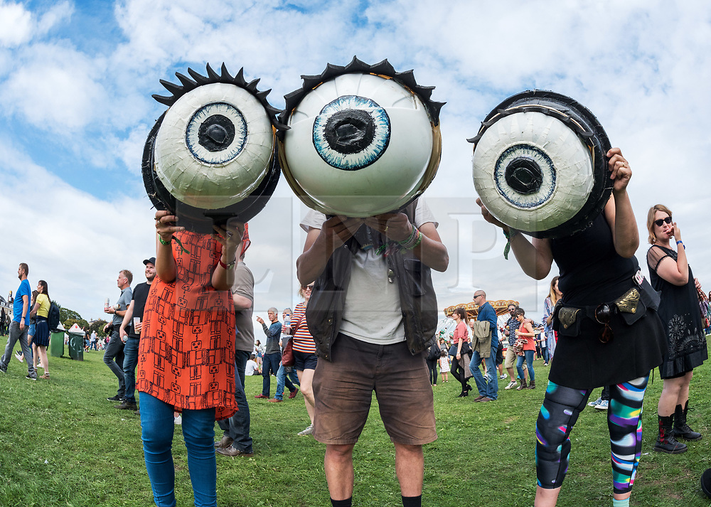 © Licensed to London News Pictures. 01/09/2018. Bristol, UK. The Downs Festival on The Downs in Bristol. Picture of #EYESCURA portable camera obscuras shaped like giant eyes entertaining the crowds. People can try one on and they will see the world upside down as in a camera obscure. The one day festival is taking place for the third year and features headliners Noel Gallagher's High Flying Birds, Paul Weller, and Orbital. Photo credit: Simon Chapman/LNP