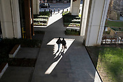 While office workers remain at home in accordance to government Covid guidelines and individual corporate policies, some Londoners walk in warm spring sunshine beneath Bassishaw Highwalk in the City of London, the capital's financial district, during the third lockdown of the Coronavirus pandemic, on 9th March 2021, in London, England.
